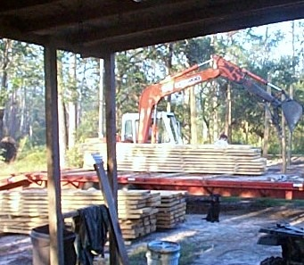 Unloading rough cut lumber with a trackhoe